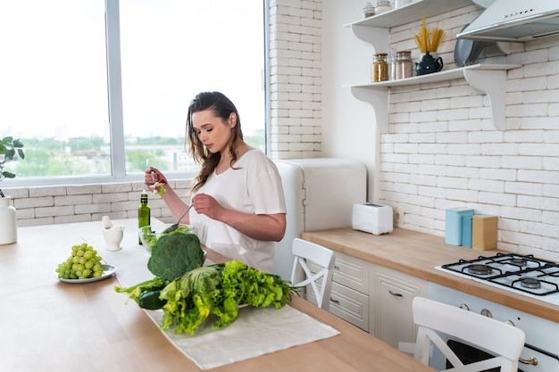 Momenti di stile di vita di una giovane donna a casa. donna che prepara un'insalata in cucina