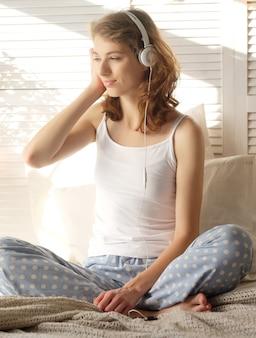 Stile di vita e concetto di persone: bella ragazza contenta in pigiama che ascolta musica usando le cuffie e balla sul letto bianco