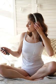 Stile di vita e concetto di persone: bella ragazza contenta in pigiama che ascolta musica usando le cuffie e balla sul letto bianco Foto Premium