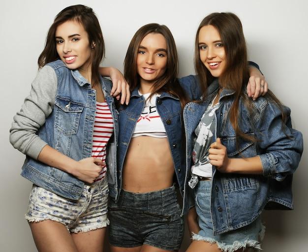 Concetto di stile di vita e persone. adatti un ritratto di tre migliori amiche di ragazze alla moda su bianco