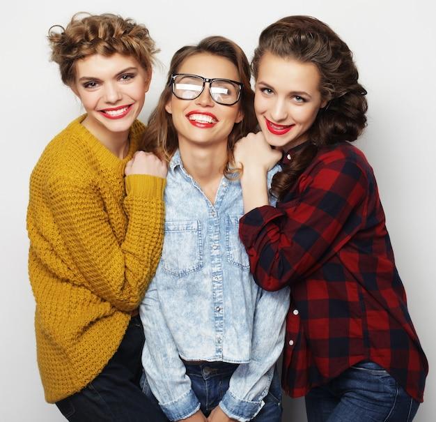 Concetto di stile di vita e persone: ritratto di moda di tre migliori amici di ragazze sexy alla moda, su sfondo bianco. momento felice per il divertimento.