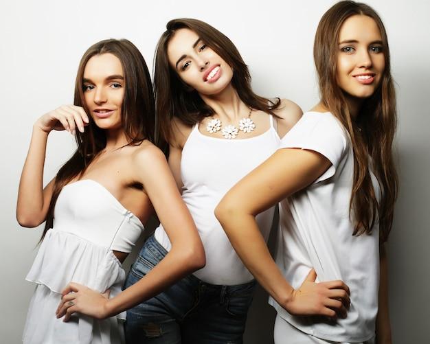 Stile di vita e concetto di persone: ritratto di moda di tre migliori amiche di ragazze sexy alla moda, su sfondo bianco. tempo felice per il divertimento.