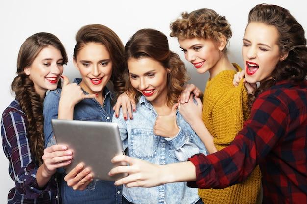 Stile di vita e concetto di persone: cinque amiche hipster che si fanno selfie con tavoletta digitale, studio girato su sfondo grigio