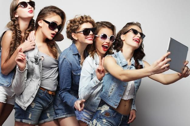 Stile di vita e concetto di persone: cinque amiche hipster che si fanno selfie con tablet digitale, studio girato su sfondo grigio