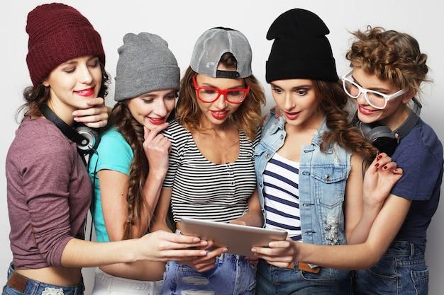 Concetto di stile di vita e persone: cinque amici di ragazze hipster che prendono selfie con tavoletta digitale, studio girato su sfondo grigio