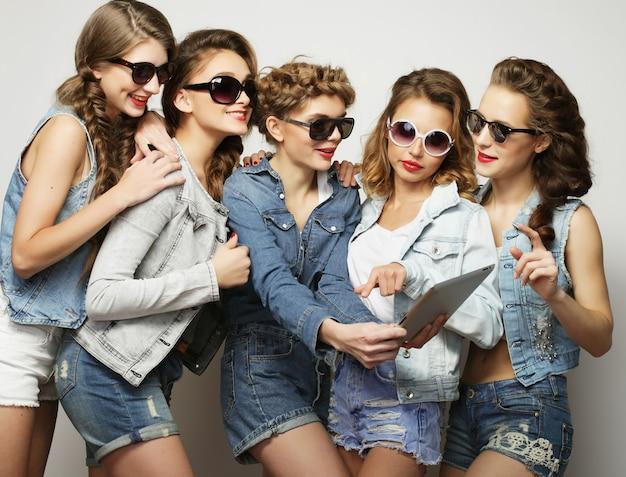 Stile di vita e concetto di persone: cinque amiche hipster che si fanno selfie con tablet digitale
