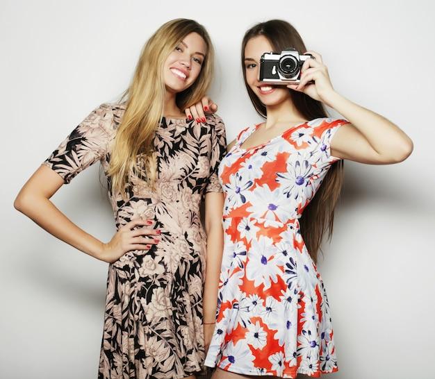 Stile di vita e concetto di persone: amiche felici che scattano alcune foto, con la fotocamera, su sfondo grigio