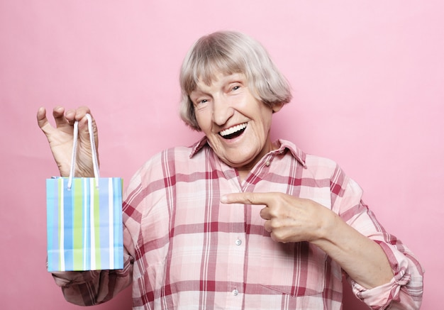 Concetto di stile di vita e persone. donna senior felice con il sacchetto della spesa sopra il rosa