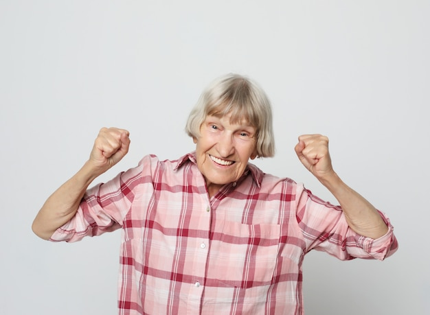 Stile di vita e concetto della gente: ritratto di una nonna allegra che gesturing vittoria