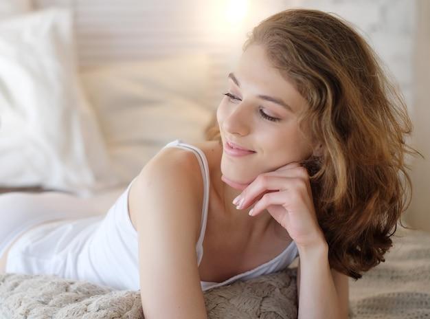 Stile di vita e concetto di persone: la bella donna bionda sta bene nella sua camera da letto. giovane signora che si gode la mattina e si sveglia.