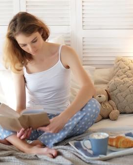 Stile di vita e concetto della gente: libro di lettura grazioso della ragazza con caffè sul letto. buongiorno.