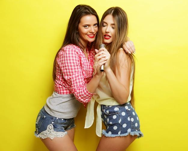 Stile di vita e concetto di persone: due amiche che stanno insieme e si divertono. su sfondo giallo.
