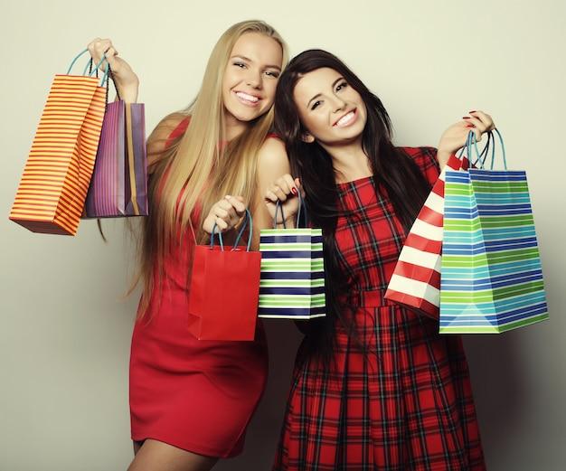 Stile di vita e concetto di persone: due giovani donne che indossano un abito rosso con borse della spesa. grande vendita.