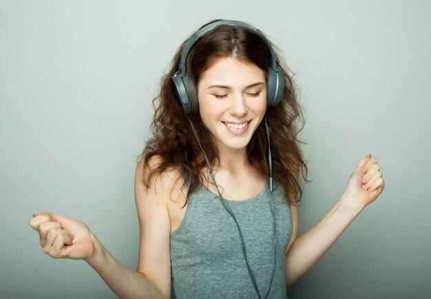 Stile di vita e concetto di persone: giovane donna felice con musica d'ascolto in cuffia.