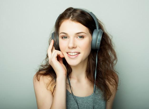 Stile di vita e concetto di persone: giovane donna felice con musica d'ascolto in cuffia. Foto Premium