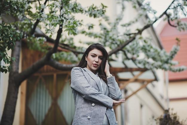Ritratto di stile di vita attraente donna elegante in posa in giacca all'esterno
