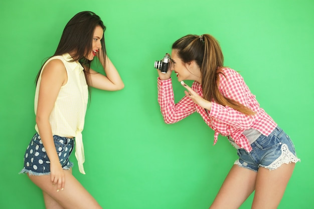 Ritratto di stile di vita di belle migliori amiche hipster ragazze in piedi insieme alla macchina fotografica e divertirsi mentre si scatta una foto. oltre il muro verde.