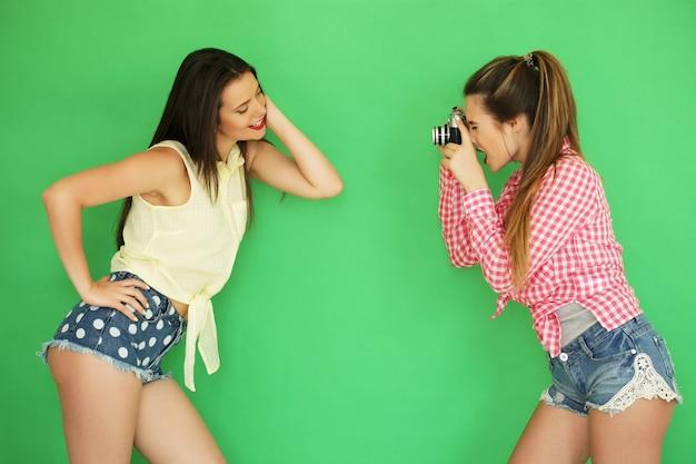 Ritratto di stile di vita di belle migliori amiche hipster ragazze in piedi insieme alla macchina fotografica e divertirsi mentre si scatta una foto