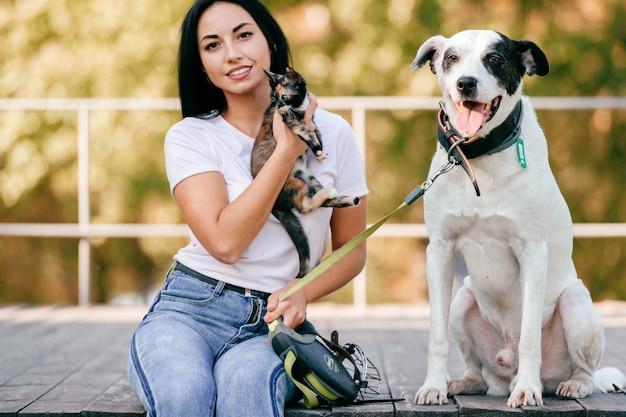 Ritratto di stile di vita di bella donna castana con la seduta del piccolo gatto e del grande cane all'aperto nel parco.