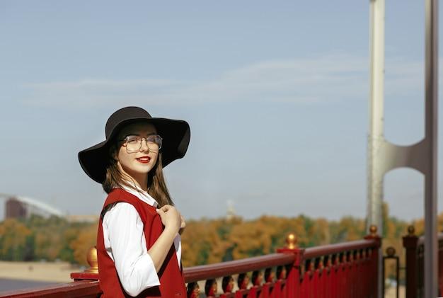 Il ritratto di stile di vita di una donna elegante indossa un costume rosso, un cappello nero, occhiali alla moda. spazio per il testo