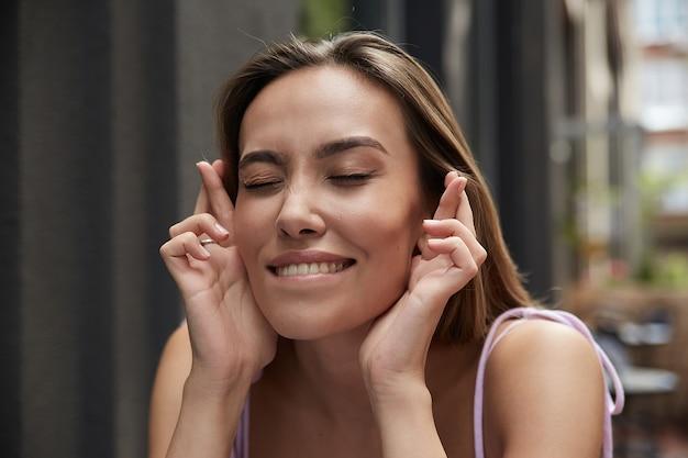 Ritratto di stile di vita di giovane donna asiatica attraente sorridente che tiene le dita incrociate per buona fortuna, mordendosi il labbro inferiore. emozionale sorridente divertente bella femmina che augura fortuna con gli occhi chiusi all'aperto