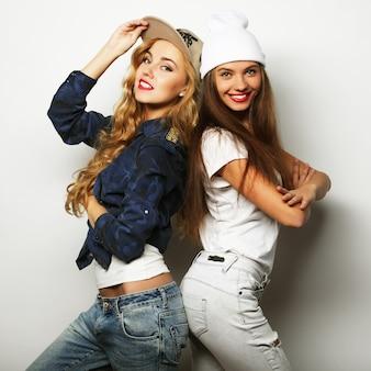 Ritratto di stile di vita di due amiche piuttosto adolescenti che sorridono e si divertono, indossano abiti e cappelli hipster, umore positivo.