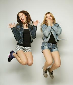 Ritratto di stile di vita di due giovani ragazze hipster migliori amiche saltano su sfondo grigio