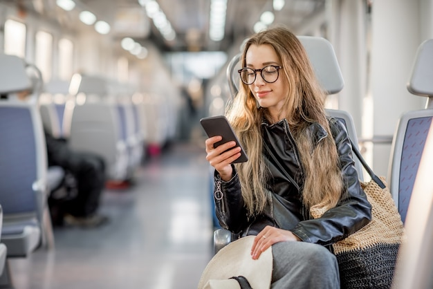 Ritratto di stile di vita di una giovane donna d'affari seduta con uno smartphone al treno moderno