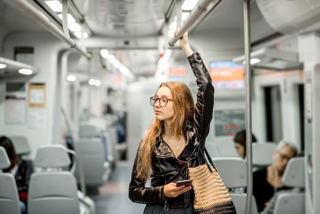 Ritratto di stile di vita di una giovane donna d'affari in piedi con lo smartphone al treno moderno