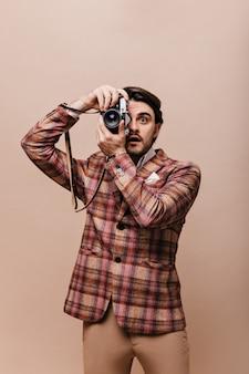 Ritratto di stile di vita di un giovane fotografo in blazer scozzese vintage e pantaloni che tengono la macchina fotografica e fanno foto