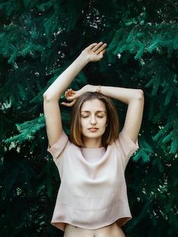 Ritratto di stile di vita di giovane donna bianca con i capelli corti in piedi davanti al pino con gli occhi chiusi e le mani sollevate