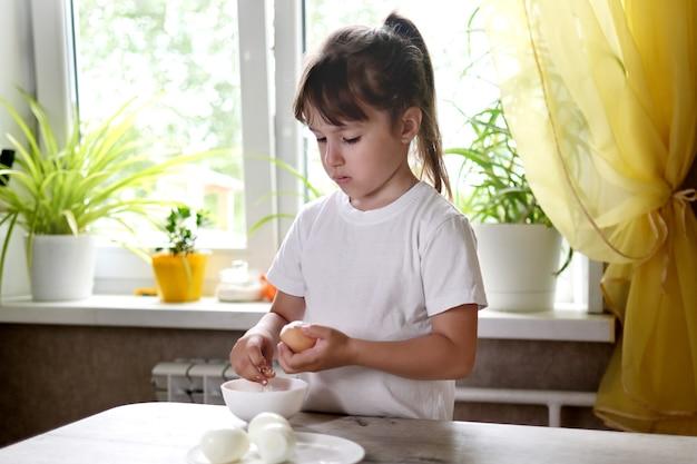 Stile di vita bambino in età prescolare ragazza cucinare cibo in cucina. sviluppo delle capacità motorie fini nella vita quotidiana da materiali di scarto. bambino pulisce le uova.