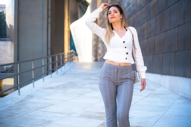 Stile di vita, una bella ragazza bionda con la camicia bianca che cammina con i tacchi