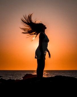 Stile di vita, silhouette di una giovane bionda sulla costa su un tramonto muovendo i capelli, con il sole