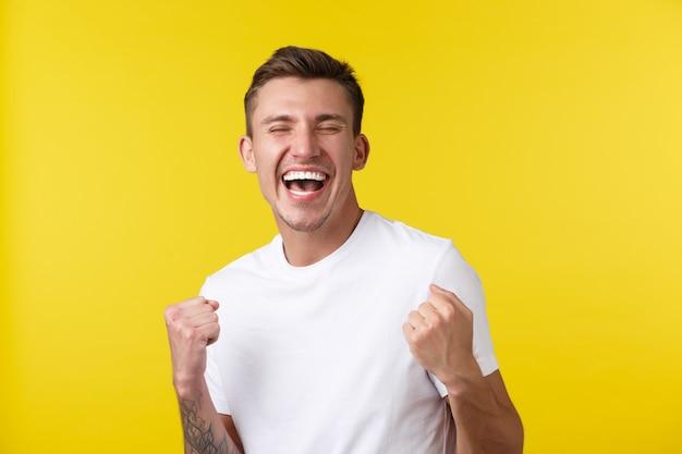 Stile di vita, estate e concetto di emozioni delle persone. ritratto ravvicinato di un bel ragazzo felice che si rallegra che si sente sollevato per le ottime notizie, raggiungere l'obiettivo o vincere un premio, sfondo giallo.