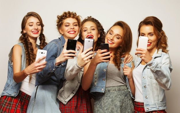 Stile di vita, tecnologia e concetto di internet: un gruppo di giovani donne che guardano i loro smartphone