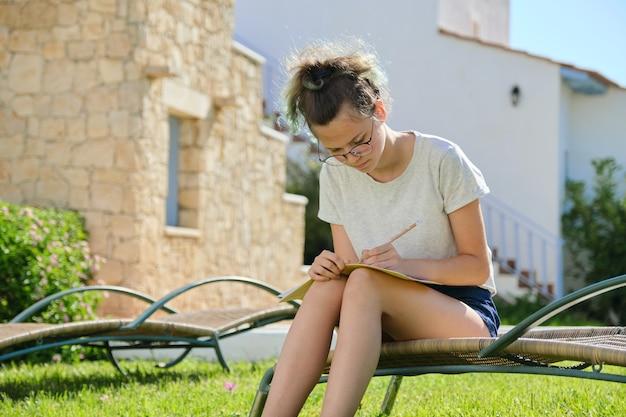 Stile di vita di un'adolescente di 15, 16 anni, ragazza seduta su un lettino da giardino sull'erba, scrive studiando nel quaderno di scuola. prato vicino a casa, giorno d'estate