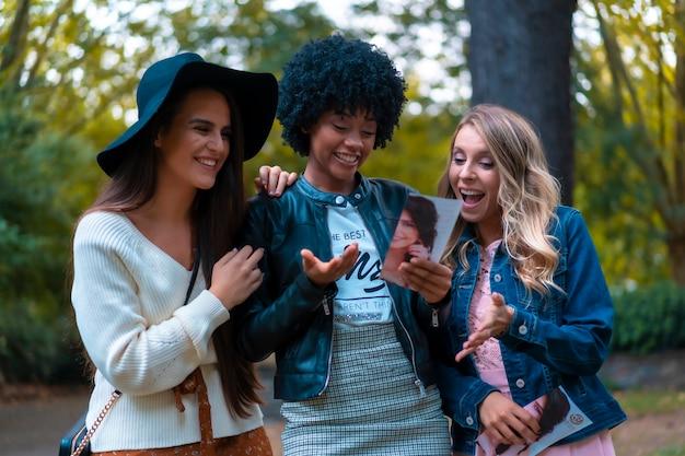 Stile di vita. tre giovani amici che allucinano con un volantino del parco, una bionda, una bruna e una ragazza latina con i capelli afro