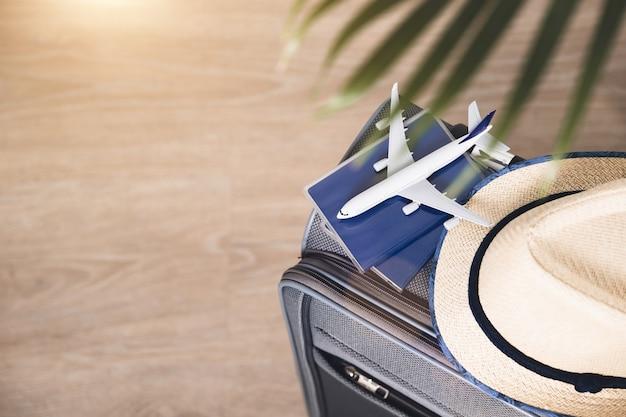 Stile di vita e concetto di viaggio. passaporti, cappello e modello di aeroplano sulla valigia grigia