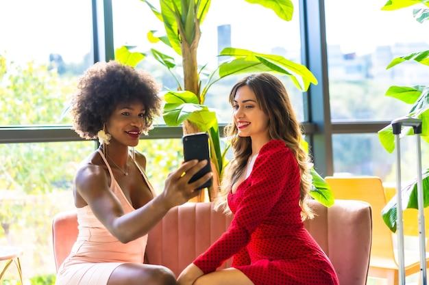 Lifestyle, due amiche sono recentemente arrivate in hotel con le loro valigie realizzando un video per i social, una bionda caucasica e una ragazza nera con i capelli afro, un vestito rosa e un vestito rosso.