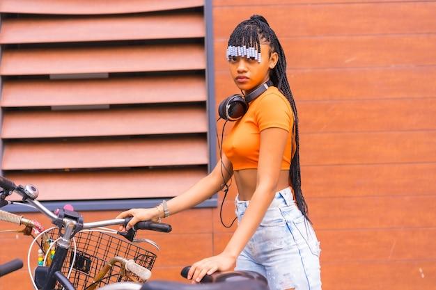Stile di vita con una giovane ballerina trap in città. ragazza nera grind di gruppo etnico africano con camicia arancione in città. cofing la bici parcheggiata in città