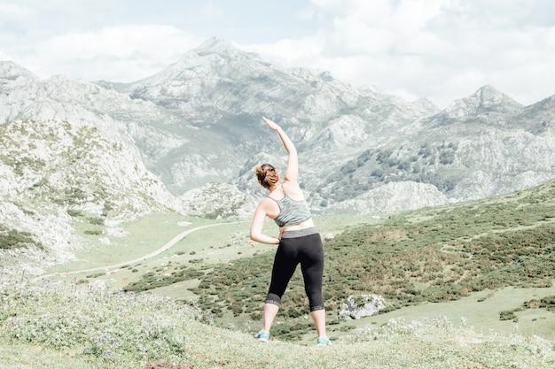 Esercizio e posa della donna di stile di vita per una vita sana. la ragazza o le persone posano lo zen vitale del corpo dell'equilibrio e la meditazione per lo sfondo della montagna della natura di allenamento. copia spazio per banner.