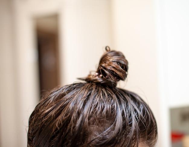 La donna di stile di vita dipinge i capelli grigi dell'henné, cura di sé la colorazione dei capelli. cura dei capelli a casa. la donna si è applicata una maschera o un balsamo sui capelli.