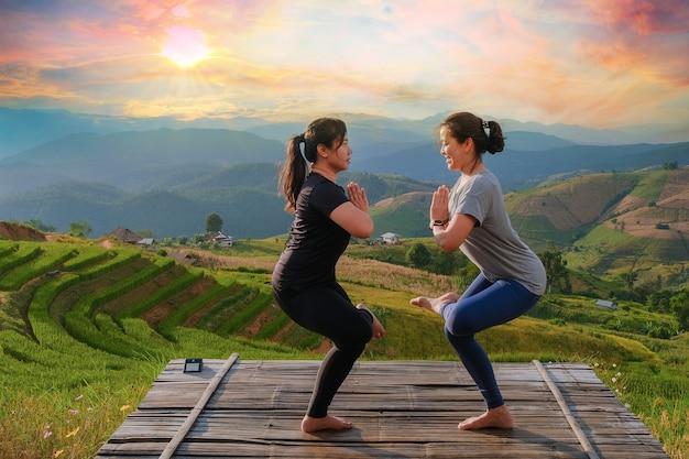 Lo stile di vita di una donna che pratica la meditazione e lo yoga energetico zen all'aperto la sera su un ponte in mezzo alla natura di montagna. con il tramonto