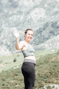 La donna dello stile di vita saluta la macchina fotografica, l'esercizio e la posa per una vita sana. la ragazza o le persone posano lo zen vitale del corpo dell'equilibrio e la meditazione per lo sfondo della montagna della natura di allenamento. copia spazio per banner.