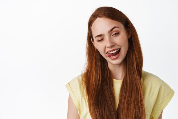 Stile di vita e donne. primo piano di una ragazza dai capelli rossi che fa l'occhiolino e mostra la lingua, resta positivo, sembra felice e ottimista, in piedi in maglietta su bianco
