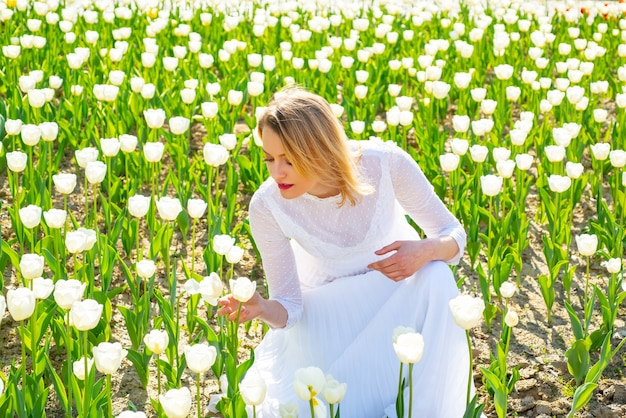 Le donne dello stile di vita si sentono bene rilassate e felici nella libertà nella fattoria dei tulipani della natura.