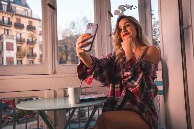 Stile di vita di una giovane bionda che fa colazione accanto alla vendita della sua casa. vestita in pigiama, saluta in una videochiamata il suo ragazzo
