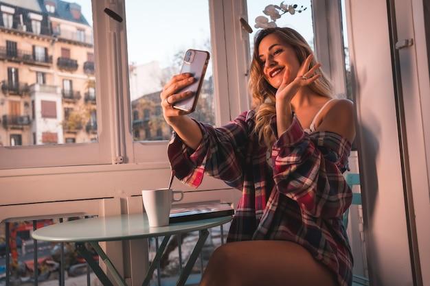 Stile di vita di una giovane bionda che fa colazione accanto alla vendita della sua casa. vestito in mutande e pigiama, saluto in videochiamata il tuo ragazzo