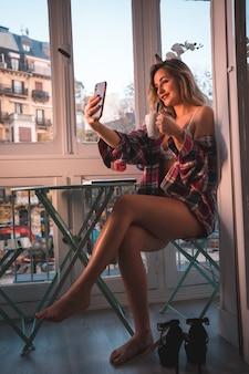 Stile di vita di una giovane bionda che fa colazione accanto alla vendita della sua casa. vestito in mutande e pigiama, guardando i social network